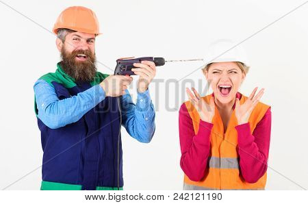 Husband Annoying His Wife. Man With Happy Face Drills Head Of Woman, White Background. Builder, Repa