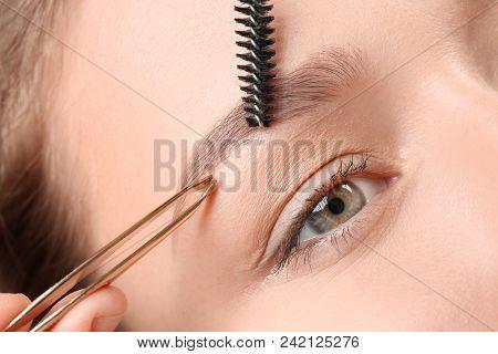 Young Woman Having Eyebrow Correction Procedure In Beauty Salon, Closeup