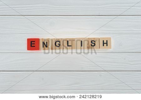 Top View Of English Word Made Of Wooden Cubes On White Wooden Tabletop