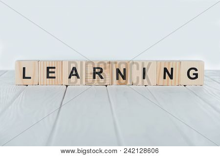 Close Up View Of Learning Word Made Of Wooden Cubes On White Wooden Tabletop