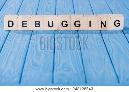 Close Up View Of Debugging Word Made Of Wooden Blocks On Blue Tabletop