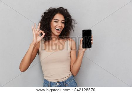 Portrait of a smiling young african woman holding blank screen mobile phone and showing ok over gray background