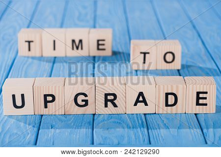 Close Up View Of Arranged Wooden Blocks Into Time To Upgrade Phrase On Blue Wooden Surface
