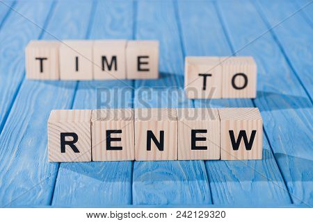Close Up View Of Arranged Wooden Blocks Into Time To Renew Phrase On Blue Wooden Surface