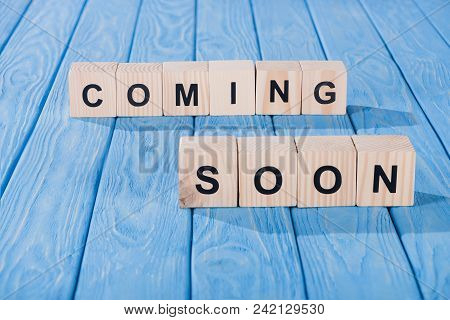 Close Up View Of Arranged Wooden Blocks Into Coming Soon Phrase On Blue Wooden Surface