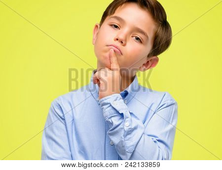 Handsome toddler child with green eyes doubt expression, confuse and wonder concept, uncertain future over yellow background