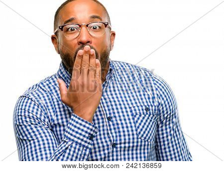 African american man with beard covers mouth in shock, looks shy, expressing silence and mistake concepts, scared isolated over white background