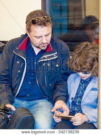 Portrait Of A Mature Father With A Cute Little Son In A Train Playing A Game On A Smartphone