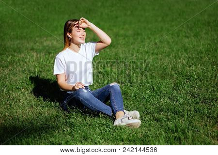 Portrait Of A Pretty Young Woman Relaxing On A Green Grass.