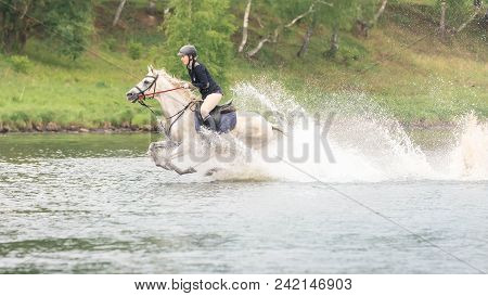 May 20, 2018. Moscow. Horsewoman On A White Horse Forces The River In The Summer. Wood On  Backgroun
