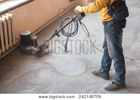 Workers Grind The Concrete Floor At The Construction Site