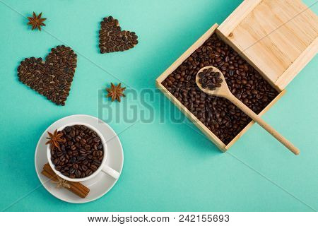 Cup Of Coffee Seeds, Cinnamon, Anis Coffee Heart Shapes, Wooden Box And Spoon With Coffee    On Cyan