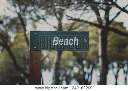 Pointer To The Beach In The Form Of A Wooden Tablet Close-up