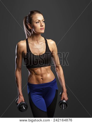 Sporty Woman Does The Exercises With Dumbbells On Dark Background. Photo Of Muscular Woman In Sports