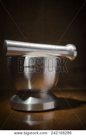 Metal Mortar With Pestle On A Wooden Table