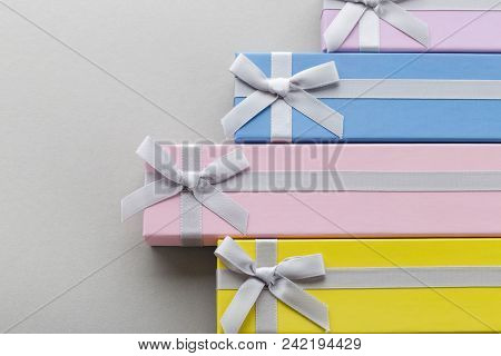 Colorful Present Boxes With Ribbon Bows On Gray Background. Pink, Yellow, Blue And Violet Long Gift