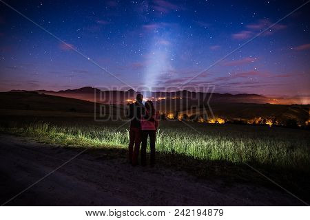 Young Happy Couple Hugging At Starry Night In Mountains. Pointing Flashlight Light To The Sky. Freed