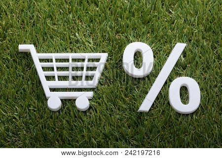 High Angle View Of White Miniature Shopping Cart And Percentage Sign On Green Grass