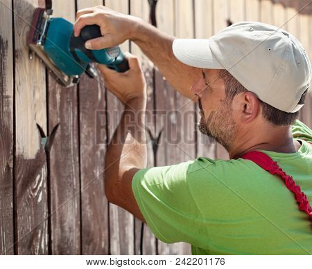 Sideview Of Worker Using Vibrating Sander Machine Scraping Off Old Paint From A Wooden Fence