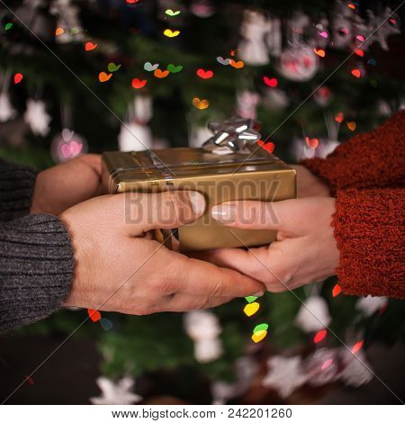 Giving A Gift With Love - Male And Female Hands Holding A Present On Dark Background With Heart Shap