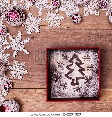 Christmas Present Concept With Xmas Tree Drawing In Flour On Giftbox Bottom And Decorations Frame