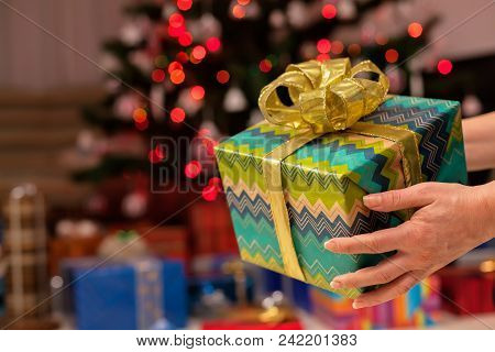 Christmas Gift In Woman Hand Closeup - Decorated Tree With More Presents In Background