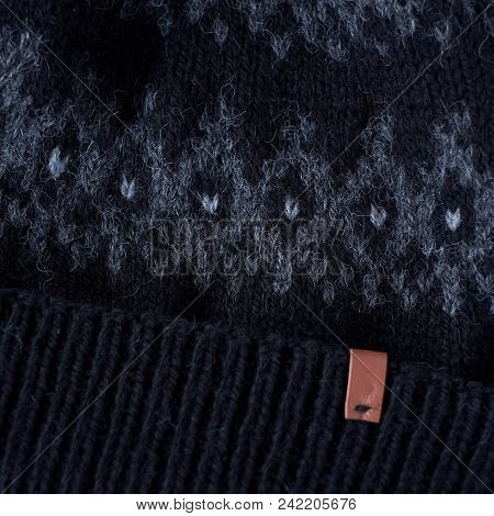 Gray Winter Hat With A Jacquard Pattern On A Gray Background Closeup.