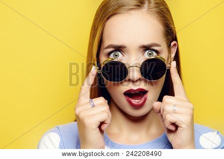 Funny young woman is looking over the sunglasses on a yellow background. Optics, sunglasses.