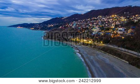 Drone View Of The Seaside With The Illuminated District Of The City Of Sochi At Twilight, Russia
