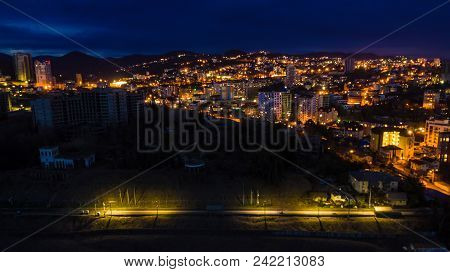 Drone View Of The Seaside With The Illuminated District Of The City Of Sochi At Dusk, Russia