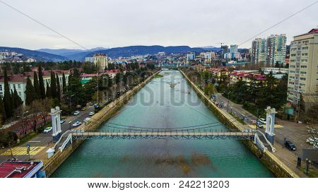 Drone View Of Malyy Kubanskiy Bridge Over Sochi River, Buildings And Streets Of The City Of Sochi In