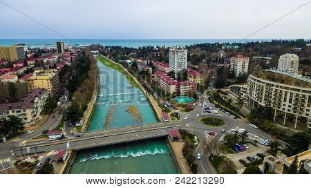 Drone View Of Kubanskiy Bridge Over Sochi River, Buildings And Streets Of The City Of Sochi In Cloud