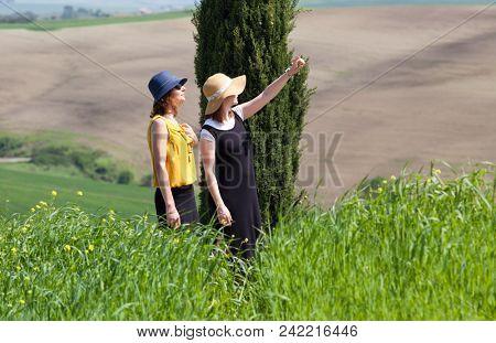 two women admiring green summer landscape