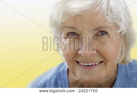 Natural senior woman portrait on yellow background