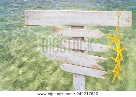 Rustic White Empty Wood Signs With Yellow Starfish Over Fresh Green Ocean Water At Es Trenc, Mallorc