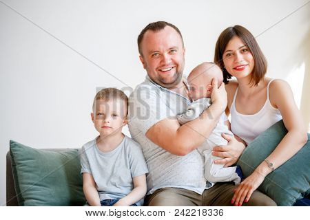 Image of couple with two young sons sitting on sofa