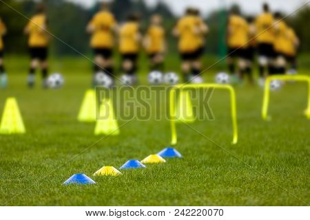 Football Training Session. Soccer Balls, Pylons, Cones, Marks And Training Hurdles On Grass Pitch. Y