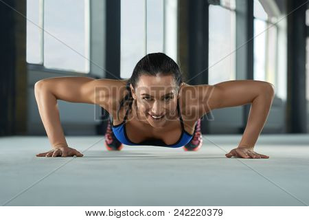Frontview of girl with athletic body doing push ups on the gym floor. Having sturdy muscles, healthy body and tanned skin. Looking strong, fit, feeling good. Wearing comfortable stylish sportswear. poster