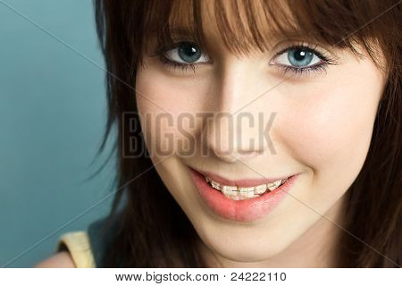 Beautiful young teenager with braces on her teeth, smiling happy