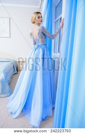 Full length portrait of a magnificent young woman in elegant long blue dress. Luxurious apartments.  Wedding fashion.
