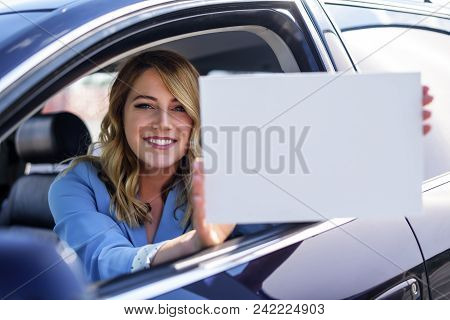 Woman Sitting In The Car And Holding A White Blank Poster. Attractive Blonde With A Clean Sheet Of P