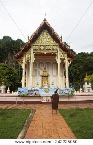 Thai Monk Walking At Wat Tham Khuha Sawan In Phatthalung, Thailand
