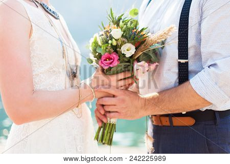 Bride And Groom With Wedding Bouquet Are On Beach Near Blue Sea After Ceremony. Bridal Dress Is Whit