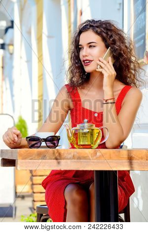 Charming brunette woman with beautiful smile using her smartphone while resting and drinking tea in a summer caf?.