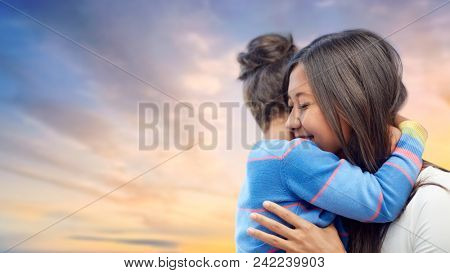 family, motherhood and people concept - happy mother and daughter hugging over evening sky background