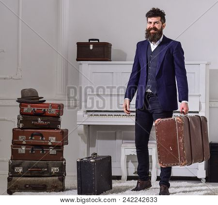 Macho Elegant On Smiling Face Stands Near Pile Of Vintage Suitcase, Holds Suitcase. Man, Traveller W