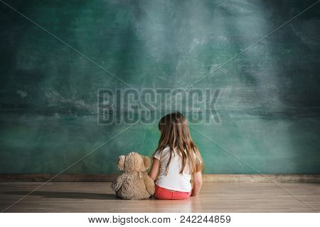 Little Autistic Girl With Teddy Bear Sitting On Floor At Empty Room. Autism Concept. Conceptual Imag