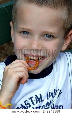 Little Boy Eats A Pretzel While Visiting A County Fair.  He Is Smilng And His Eyes Are Shining.