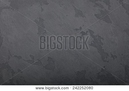 Grunge dark grey faded uneven old aged daub plaster wall texture background with stains and paint strokes, close up poster