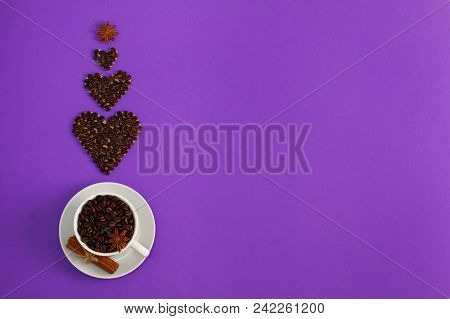 Cup Of Coffee Seeds And Three Coffee Heart Shapes With Spices Cinnamon, Anis On Purple Background. I